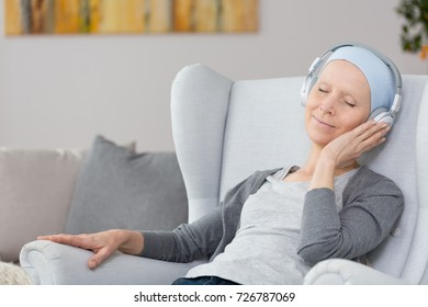 Woman with cancer sitting in a blue armchair, wearing big wireless headphones, and listening to relaxing music