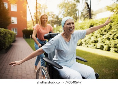 A woman with cancer is sitting in a wheelchair. She walks on the street with her daughter and they fool around. They are fun and they laugh. They walk in the courtyard of the clinic.