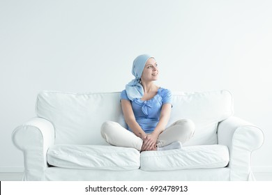Woman with cancer smiling joyously while sitting cross-legged on a couch