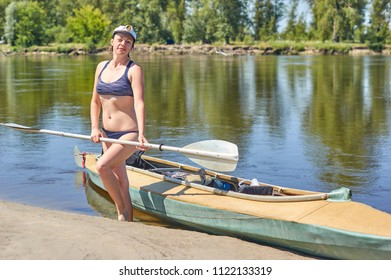 Woman with a canoe on the beach.Happy athletic woman having fun enjoying adventurous experience on the river on a sunny day during summer holidays/Beautiful woman paddling in canoe