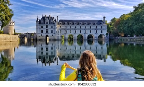 A woman canoeing toward Chateau de Chenonceau in Loire Valley, France
