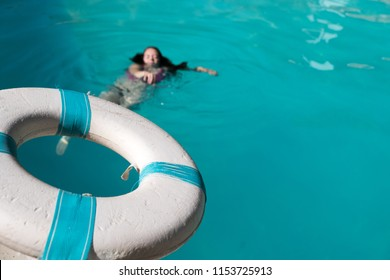 Woman can't swim and is drowning in a swimming pool outside. Cry for help, man holds out life preserver to save girl from drowning in outdoor swimming pool.