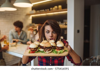 Woman can't wait to eat all the hamburgers in the kitchen.