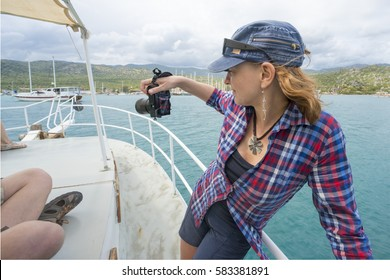 Woman in cap with camera on a white yacht in the sea