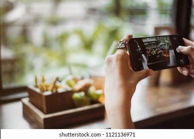 woman capturing photos of food.