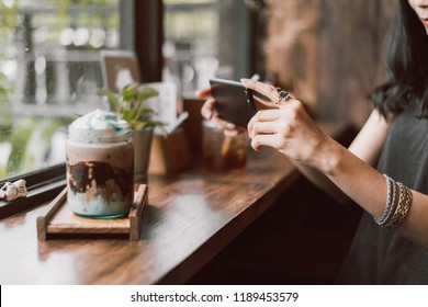 woman capturing photos of ice chocolate.