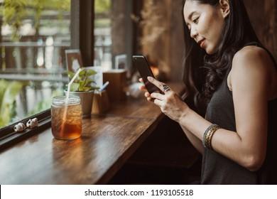 woman capturing photos of ice tea.