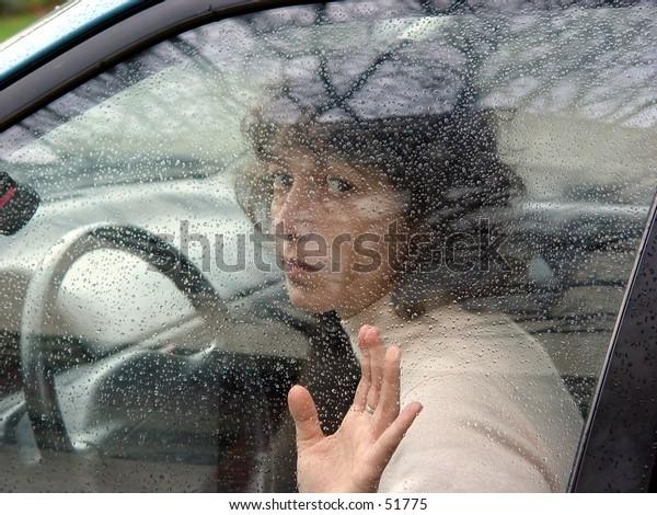 A woman in a car behind the wheel.