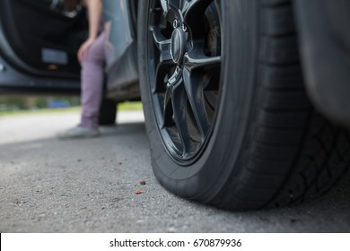 Woman with car broken down, flat tire, close up