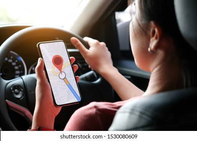 A woman car driving on the road And she is looking for a GPS map on a smartphone to get to the destination of the route. Concept of technology and road traffic