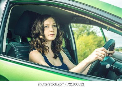 Woman in the car. Hands on the wheel. Focused and tense. The lesson in driving school.