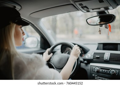 woman in car indoor keeps wheel turning around smiling looking at passengers in back seat idea taxi driver. Concept of exam Vehicle.
