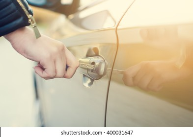 Woman with car key. Opening car door. Woman´s hand unlock a door on a car. Sunlight. Transportation.