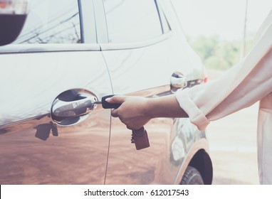 Woman with car key opens the door to a car.
