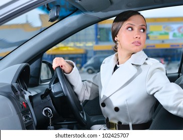 woman in a car is looking backwards trying to move back