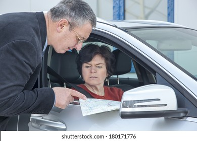 Woman with car and map asks for the way