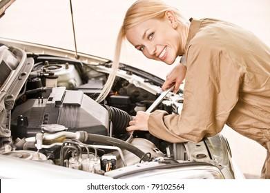 Woman car mechanician repairs engine of car and smiles.
