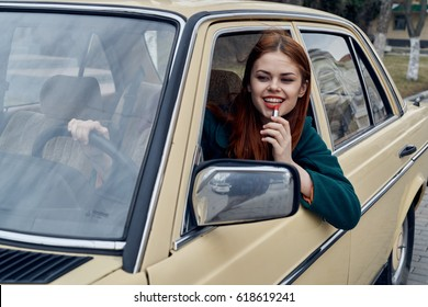 Woman in the car, the woman paints the lips at the wheel of the car