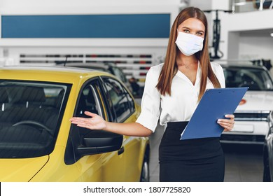 Woman car seller standing near new car wearing protective face mask