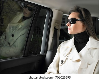 Woman in car, sunglasses on