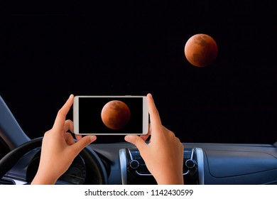 woman in the car use mobile phone take photo of lunar eclipse on the dark sky