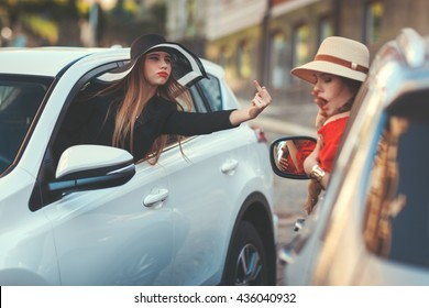 Woman from the car window showing a rude gesture to another driver woman.