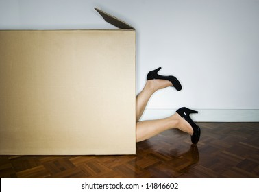 Woman in cardboard box, heels out
