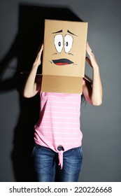 Woman with cardboard box on her head with sad face, on grey background