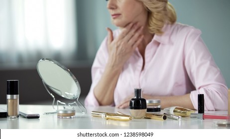 Woman carefully examining her aging and sagging skin pondering about lifting