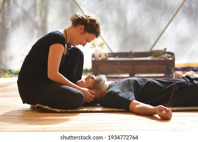 Woman caressing her relaxed and lying lover, Tantra massage practice