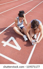 Woman caring about runner with sports injury on running track