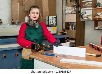 Woman carpenter with drill machine constructing furniture