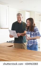 Woman With Carpenter Looking At Plans For New Kitchen