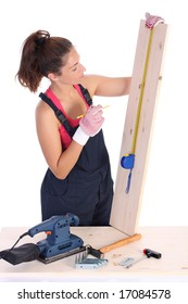 woman carpenter with wooden plank and measuring tape