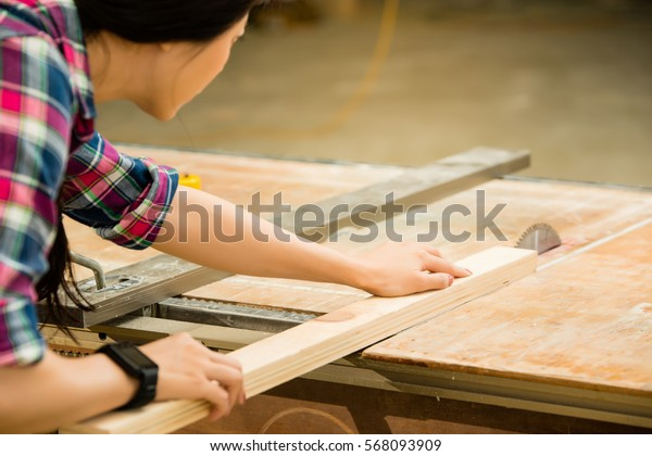woman carpenter working on an electric buzz saw cutting some boards wearing smartwatch. mixed race asian chinese model.