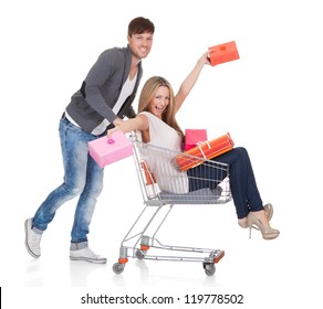 Woman carried by push cart held by man.