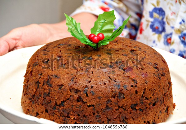 A woman carries a delicious Christmas pudding or cake.