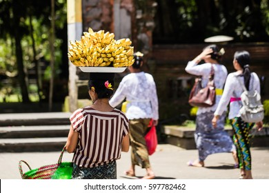 Woman carries a tray with bananas on her head in Ubud, Bali