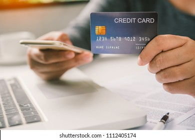 Woman carry a credit card in their hands and find information about a product using their mobile device to make purchases online and conduct financial transactions.