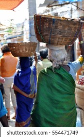 woman carrying basket on head in India