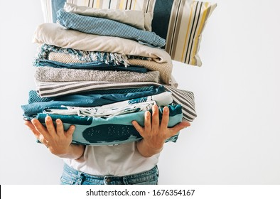Woman carrying the big pile blue and beige laundry in her hands. Woman's Home work concept image.