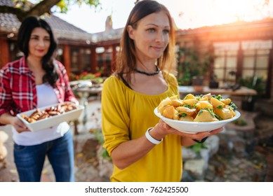 Woman carrying a bowl with roasted potatoes at backyard patio