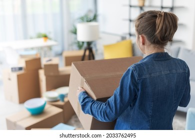 Woman carrying boxes in her new apartment, home relocation concept