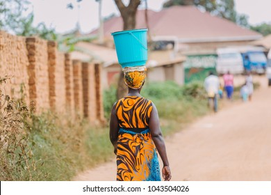 woman carrying a bucket on her head in Uganda