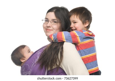 Woman carrying her little daughter in a sling. Her son hugging her from behind