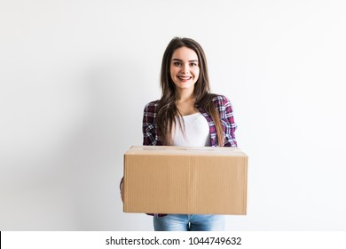 Woman carrying moving boxes. Young woman moving house to new home holding cardboard boxes in new hause