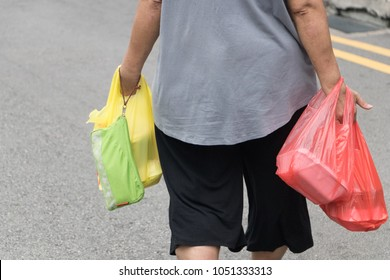 woman carrying plastic bag in her hand after shopping at street market in downtown.Inside the plastic bag is foam box of food