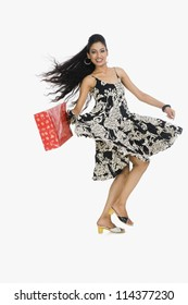 Woman carrying a shopping bag and dancing
