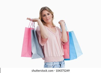 A woman is carrying shopping bags over her shoulder against a white background