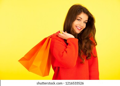 Woman carrying shopping bags over vibrant yellow background
